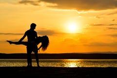 Σκιαγραφίες ζεύγους που κρατούν στο ηλιοβασίλεμα θαλασσίως, χορός Στοκ φωτογραφία με δικαίωμα ελεύθερης χρήσης
