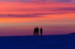Σκιαγραφίες ηλιοβασιλέματος των πορτοκαλιών σύννεφων ουρανού ανθρώπων που εξισώνουν τη νύχτα Στοκ Εικόνα