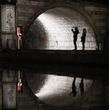 Σκιαγραφίες και αντανακλάσεις των τουριστών κάτω από μια medival γέφυρα στοκ εικόνα