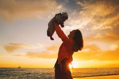 Σκιαγραφίες μητέρων και μωρών στο ηλιοβασίλεμα στην παραλία θάλασσας Στοκ Φωτογραφίες