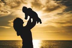 Σκιαγραφίες μητέρων και μωρών στο ηλιοβασίλεμα στην παραλία θάλασσας Στοκ εικόνα με δικαίωμα ελεύθερης χρήσης