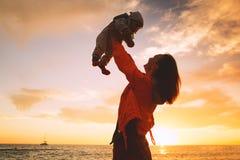 Σκιαγραφίες μητέρων και μωρών στο ηλιοβασίλεμα στην παραλία θάλασσας Στοκ Εικόνες
