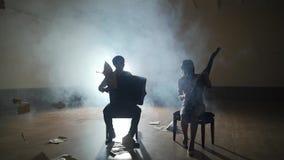 Σκιαγραφίες μουσικών που παίζουν και μειωμένα φύλλα, καπνός στο υπόβαθρο στο slowmo φιλμ μικρού μήκους