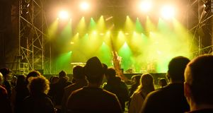 σκιαγραφίες μπροστά από τα φωτεινά φω'τα σκηνών, μουσική στοκ εικόνες