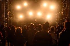 σκιαγραφίες μπροστά από τα φωτεινά φω'τα σκηνών, μουσική στοκ φωτογραφία