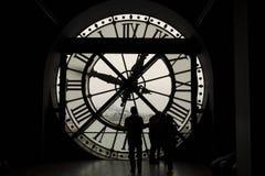Σκιαγραφίες μπροστά από το ρολόι γυαλιού στο Παρίσι Στοκ εικόνα με δικαίωμα ελεύθερης χρήσης