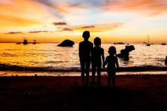 Σκιαγραφίες παιδιών στο υπόβαθρο θάλασσας ηλιοβασιλέματος Στοκ Εικόνα