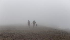 Σκιαγραφίες που περπατούν κάτω από την ομίχλη στην παραλία Στοκ φωτογραφίες με δικαίωμα ελεύθερης χρήσης