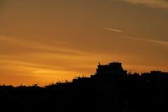 Σκιαγραφίες πόλεων scape κάτω από μια πυρκαγιά που καίει το δραματικό ουρανό Στοκ Φωτογραφία