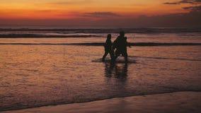 Σκιαγραφίες της ευτυχούς οικογένειας που περπατά στην παραλία κατά τη διάρκεια του όμορφου ηλιοβασιλέματος κίνηση αργή 3840x2160 απόθεμα βίντεο