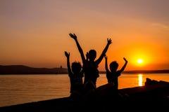 Σκιαγραφίες της μητέρας και των παιδιών στο ηλιοβασίλεμα Στοκ Εικόνες