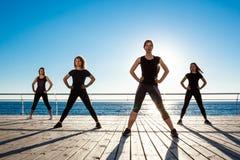 Σκιαγραφίες του αθλητικού zumba χορού κοριτσιών κοντά στη θάλασσα στην ανατολή Στοκ Εικόνες