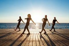 Σκιαγραφίες του αθλητικού zumba χορού κοριτσιών κοντά στη θάλασσα στην ανατολή Στοκ εικόνα με δικαίωμα ελεύθερης χρήσης
