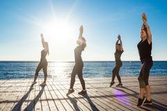 Σκιαγραφίες του αθλητικού zumba χορού κοριτσιών κοντά στη θάλασσα στην ανατολή Στοκ Φωτογραφίες