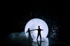 Σκιαγραφίες του ζεύγους παιχνιδιών που χορεύουν κάτω από το φεγγάρι τη νύχτα Αριθμοί του ερωτευμένου χορού ανδρών και γυναικών στ Στοκ φωτογραφίες με δικαίωμα ελεύθερης χρήσης