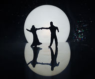 Σκιαγραφίες του ζεύγους παιχνιδιών που χορεύουν κάτω από το φεγγάρι τη νύχτα Αριθμοί του ερωτευμένου χορού ανδρών και γυναικών στ Στοκ εικόνες με δικαίωμα ελεύθερης χρήσης