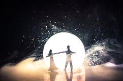 Σκιαγραφίες του ζεύγους παιχνιδιών που χορεύουν κάτω από το φεγγάρι τη νύχτα Αριθμοί του ερωτευμένου χορού ανδρών και γυναικών στ Στοκ Φωτογραφίες