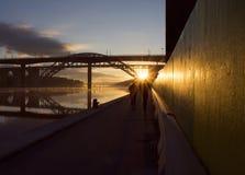 Σκιαγραφίες του ζεύγους που τρέχουν στην όμορφη, πρόωρη αυγή κάτω από μια γέφυρα Στοκ Εικόνες
