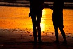 Σκιαγραφίες του ζεύγους στην παραλία κατά τη διάρκεια του ηλιοβασιλέματος Στοκ φωτογραφία με δικαίωμα ελεύθερης χρήσης