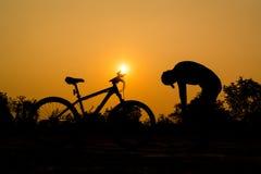 Σκιαγραφίες του ποδηλάτου βουνών με το άτομο Στοκ Εικόνες
