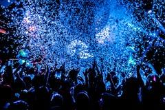 Σκιαγραφίες του πλήθους συναυλίας μπροστά από τα φωτεινά φω'τα σκηνών με το κομφετί Στοκ εικόνες με δικαίωμα ελεύθερης χρήσης