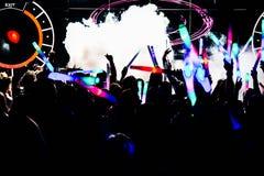 Σκιαγραφίες του πλήθους συναυλίας μπροστά από τα φωτεινά φω'τα σκηνών με το κομφετί Στοκ Εικόνα