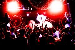 Σκιαγραφίες του πλήθους συναυλίας μπροστά από τα φωτεινά φω'τα σκηνών με το κομφετί Στοκ Φωτογραφία