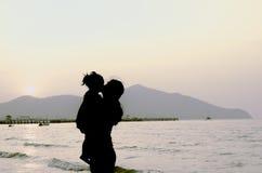 Σκιαγραφίες του φιλήματος μητέρων και μωρών στο ηλιοβασίλεμα Στοκ εικόνες με δικαίωμα ελεύθερης χρήσης