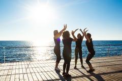 Σκιαγραφίες των αθλητικών κοριτσιών που δίνουν τη highfive κοντινή θάλασσα στην ανατολή Στοκ φωτογραφία με δικαίωμα ελεύθερης χρήσης