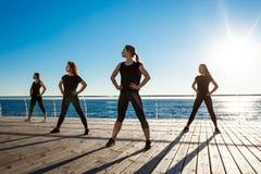 Σκιαγραφίες των αθλητικών κοριτσιών που χορεύουν κοντά στη θάλασσα στην ανατολή Στοκ Φωτογραφίες