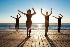 Σκιαγραφίες των αθλητικών κοριτσιών που χορεύουν κοντά στη θάλασσα στην ανατολή Στοκ εικόνα με δικαίωμα ελεύθερης χρήσης