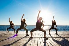 Σκιαγραφίες των αθλητικών κοριτσιών που χορεύουν κοντά στη θάλασσα στην ανατολή Στοκ φωτογραφία με δικαίωμα ελεύθερης χρήσης