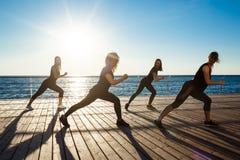 Σκιαγραφίες των αθλητικών κοριτσιών που χορεύουν κοντά στη θάλασσα στην ανατολή Στοκ Φωτογραφία