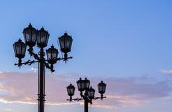 Σκιαγραφίες των λαμπτήρων οδών επεξεργασμένου σιδήρου ενάντια στο θερινό ηλιοβασίλεμα s Στοκ Φωτογραφία