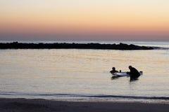 Σκιαγραφίες των ανθρώπων εν πλω στο ηλιοβασίλεμα στοκ φωτογραφίες