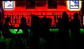 Σκιαγραφίες των ανθρώπων που κάθονται στο φραγμό Στοκ εικόνα με δικαίωμα ελεύθερης χρήσης