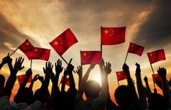 Σκιαγραφίες των ανθρώπων που κρατούν τη σημαία της Κίνας Στοκ φωτογραφία με δικαίωμα ελεύθερης χρήσης