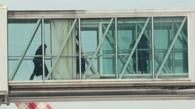 Σκιαγραφίες των ανθρώπων που περνούν στο κατάστρωμα από τη μετάβαση γυαλιού στο αεροπλάνο φιλμ μικρού μήκους