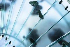 Σκιαγραφίες των ανθρώπων που περπατούν σε μια σπειροειδή σκάλα γυαλιού Στοκ εικόνα με δικαίωμα ελεύθερης χρήσης