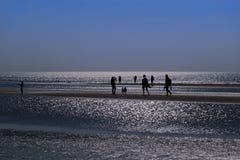 Σκιαγραφίες των ανθρώπων που περπατούν σε μια όμορφη παραλία στοκ φωτογραφία