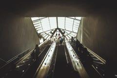 Σκιαγραφίες των ανθρώπων που προέρχονται από την κυλιόμενη σκάλα στοκ εικόνα με δικαίωμα ελεύθερης χρήσης