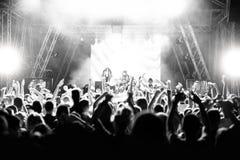 Σκιαγραφίες των ανθρώπων σε μια συναυλία μπροστά από τη σκηνή στο φωτεινό φως μαύρο λευκό στοκ φωτογραφία