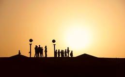 Σκιαγραφίες των ανθρώπων στην έρημο στο ηλιοβασίλεμα, πεζοπορία Στοκ Εικόνες