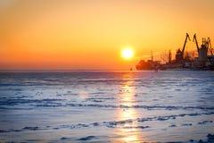 Σκιαγραφίες των γερανών και των σκαφών στην ανατολή στη θάλασσα Στοκ Εικόνες