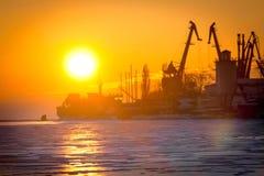 Σκιαγραφίες των γερανών και των σκαφών στην ανατολή στη θάλασσα Στοκ Φωτογραφία