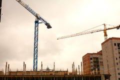 Σκιαγραφίες των γερανών πύργων ενάντια στον ουρανό βραδιού σπίτι κατασκευής κάτω βιομηχανικός ορίζοντας Στοκ Φωτογραφία