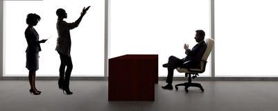 Σκιαγραφίες των θηλυκών δραστών σε μια ακρόαση με έναν πετώντας διευθυντή στοκ εικόνα με δικαίωμα ελεύθερης χρήσης