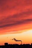 Σκιαγραφίες των κτηρίων πόλεων σε ένα υπόβαθρο του ζωηρόχρωμου κίτρινος-κόκκινου ηλιοβασιλέματος Στοκ Εικόνες