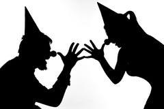 Σκιαγραφίες των κλόουν που παίζουν τις φάρσες Στοκ εικόνα με δικαίωμα ελεύθερης χρήσης