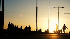 Σκιαγραφίες των νέων κοριτσιών στα σαλάχια κυλίνδρων σε ένα πάρκο στο ηλιοβασίλεμα απόθεμα βίντεο
